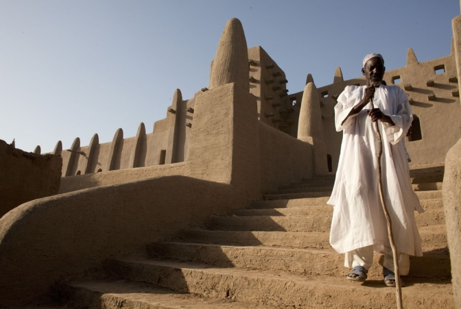 Image: A resident walks down the steps of the Great Mosque of Djenne, the largest mud-brick structure in the world, in Djenne, Mal.