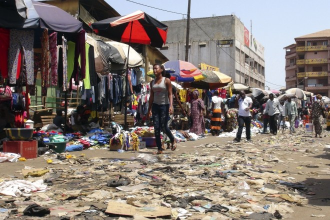 A woman walks past garbage near shops on a street in Conakry, where about 20 people were confirmed infected. Reuters